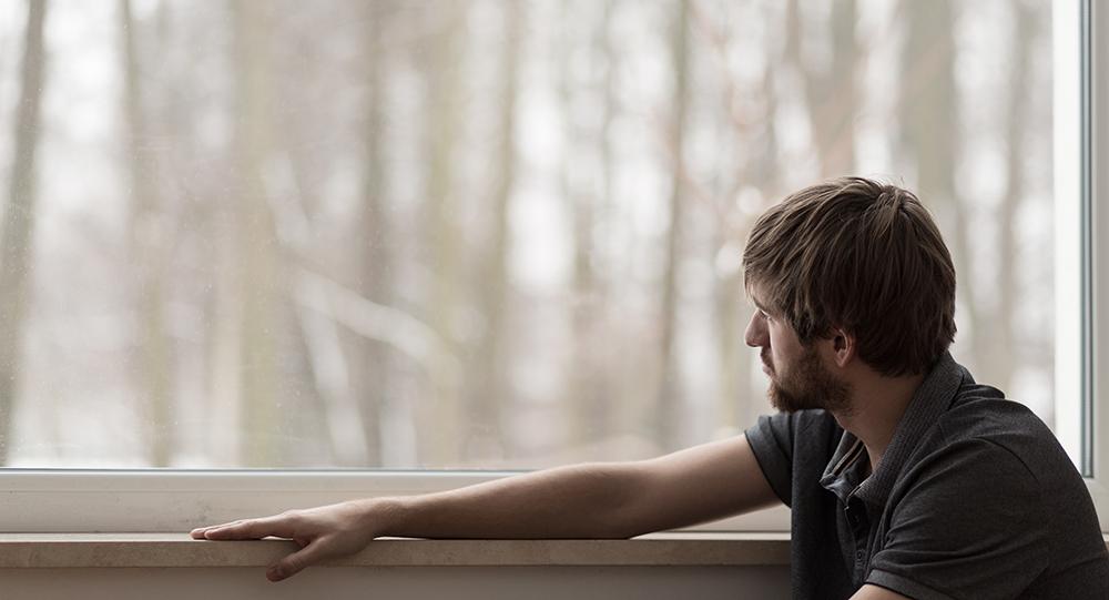 Homme déprimé regardant à travers la fenêtre