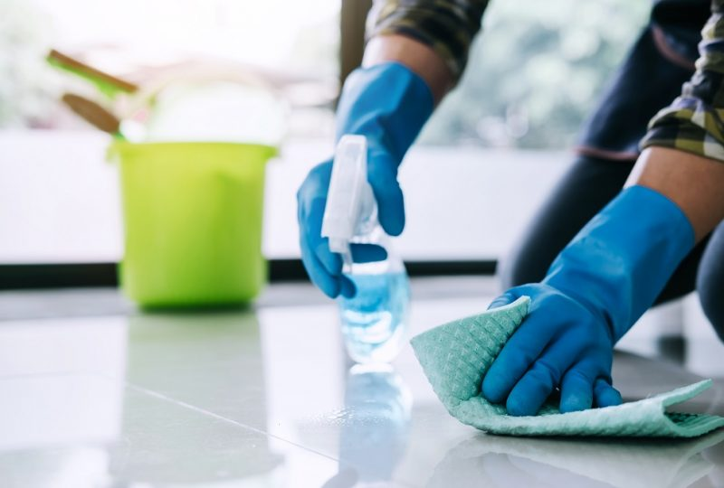 Husband housekeeping and cleaning concept, Happy young man in blue rubber gloves wiping dust using a spray and a duster while cleaning on floor at home.
