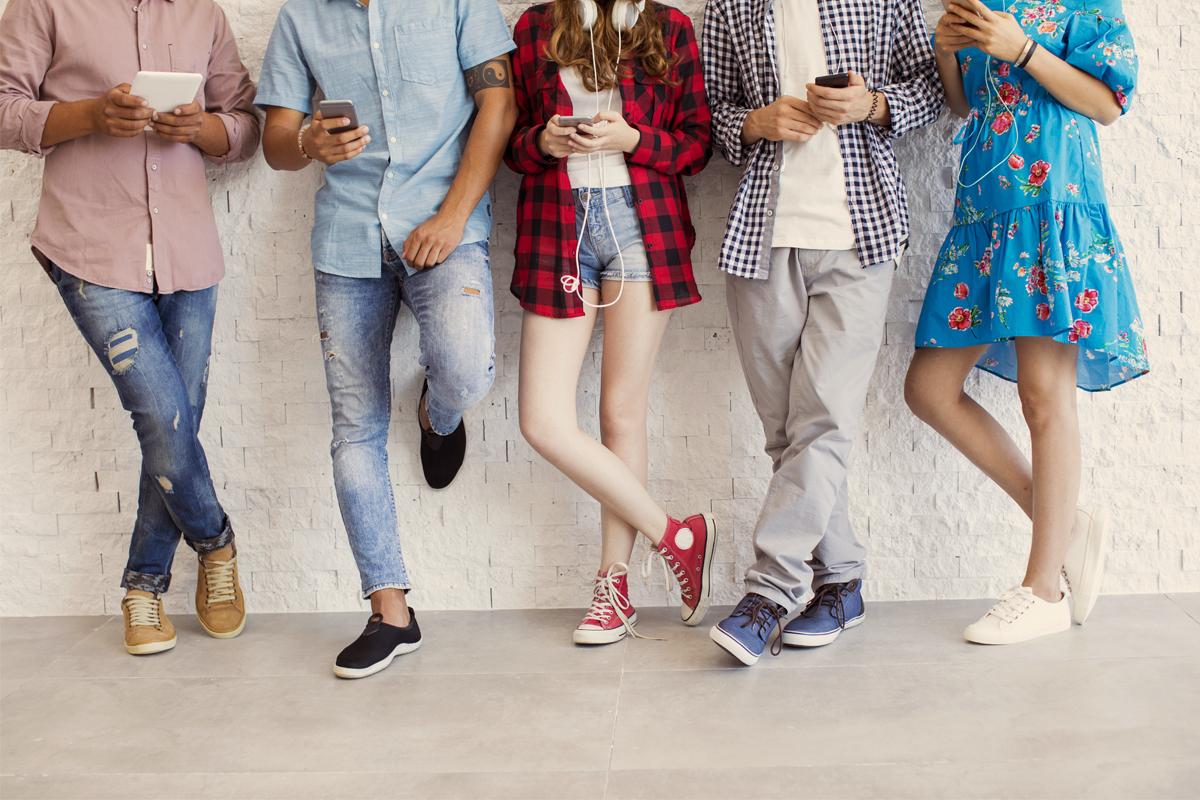 Des jeunes accotés sur un mur qui regardent leur téléphone.