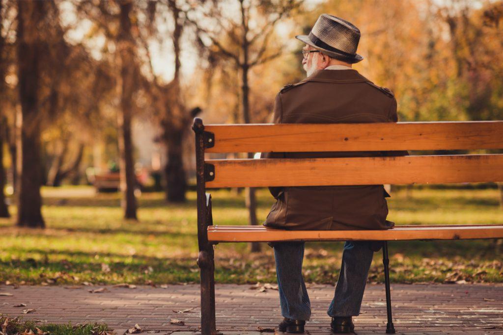 Homme veuf installé sur un banc de parc.