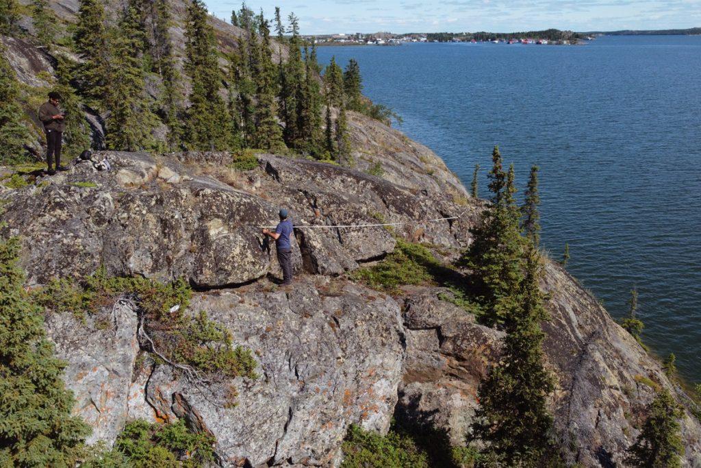 Prise de mesures sur le bord d'un affleurement en bordure du Grand lac des Esclaves à Yellowknife.