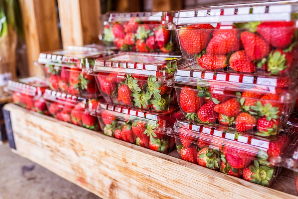 A display of plastic strawberry containers at the market.