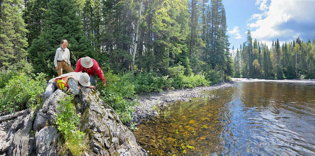 géologues au travail sur un affleurement près d'une rivière
